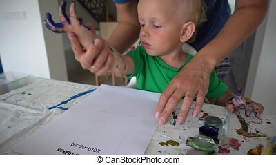 Mother and toddler son make hand print stamp on paper with watercolor