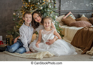 Mother and two childre under Christmas tree