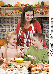 Mother and two children at Halloween making treats and smiling