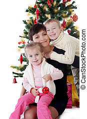 Mother and two children hugging under Christmas tree