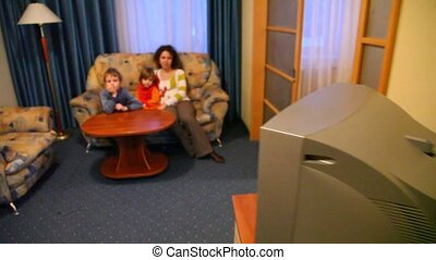 Mother and two children look TV