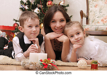 Mother and two children lying under Christmas tree