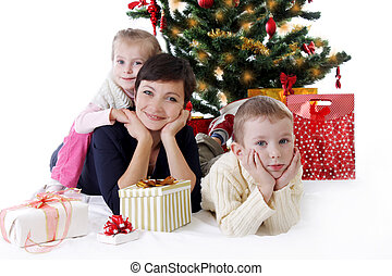 Mother and two children lying under Christmas tree with presents
