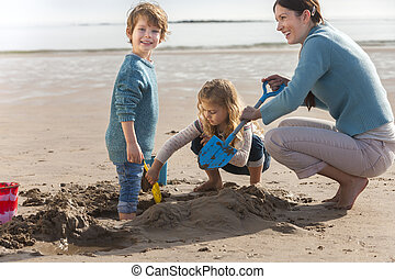 Mother and Two Children on the Beach - Mother playing on the...