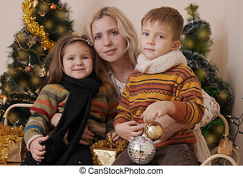 Mother and two children over Christmas tree