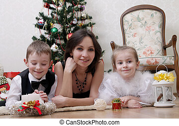 Mother and two children under Christmas tree