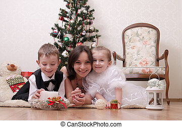 Mother and two children under Christmas trree