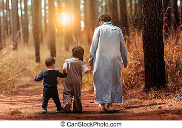 mother and two children walking in pine wood