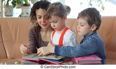 Mother and two children with book