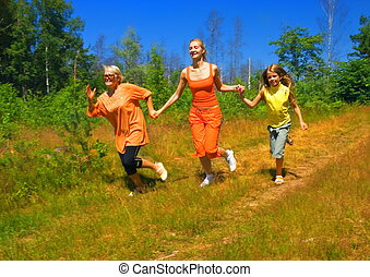 Mother and two daughters running in the forest