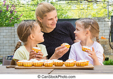 Mother and two daughters sitting at the table with Easter cupcakes in his hands