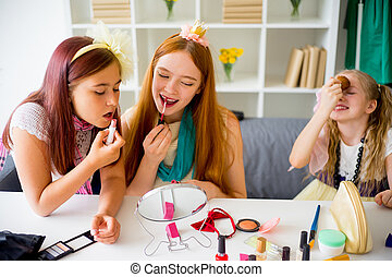 Mother and two daughters trying makeup