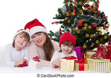 Mother and two daughters under Christmas tree