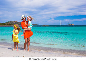 Mother and two kids at beach on sunny day