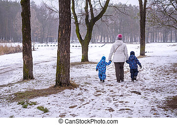 Mother and two kids having fun outdoors. Walking winter forest first snow