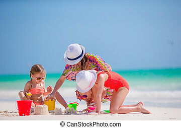 Mother and two kids playing with sand on tropical beach. Family make a new castle.