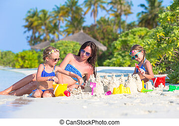 Mother and two kids playing with sand on tropical beach