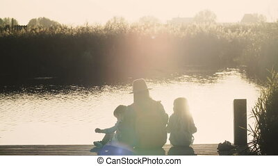 Mother and two kids sit on lake pier at sunrise. Peace and...