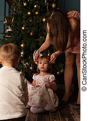 Mother and two kids sitting near Christmas tree