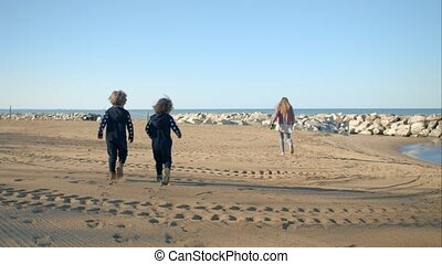 Mother and two sons are walking along the seashore