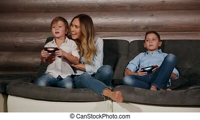 Mother and two sons sitting on the sofa in his house playing video games with wireless joystick. Happy people in the house.