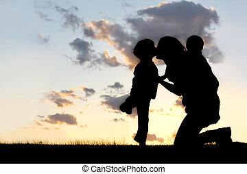 the Silhouette of a mother and her two young children; a little boy and his baby brother are playing outside at sunset, hugging and kissing.