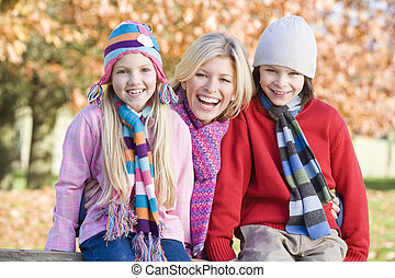 Mother and two young children outdoors in park smiling