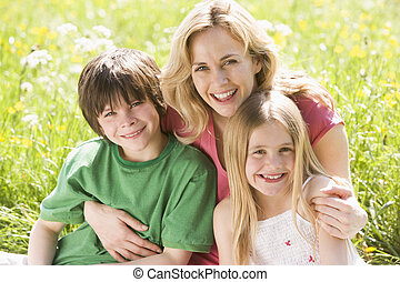 Mother and two young children sitting outdoors smiling
