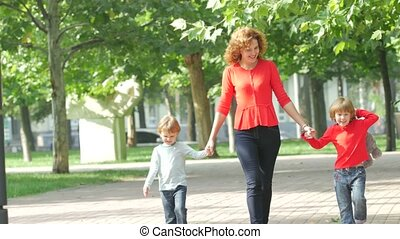 Mother and two young children walking on path holding hands smiling
