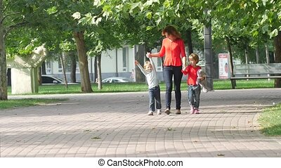 Mother and two young children walking on path holding hands smiling. Slow motion