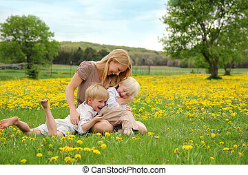Mother and Young Children Sitting in Flower Meadow Laughing