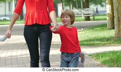 Mother and young children walking on path holding hands smiling. Close up