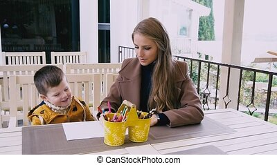 mother and young son are drawing at a table