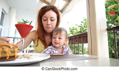 mother and young son are eating in the restaurant