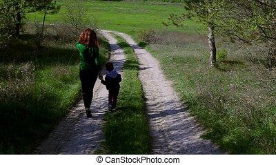 mother and young son go on the road in the forest