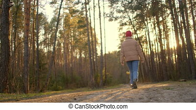 Mother And Young Son Go On The Road In The Forest. Woman and children taking a walk at the woods promenade. A happy family walks in the woods enjoying nature. 2 year old boy walks in the woods.