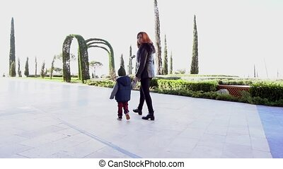 mother and young son walk through the Park 1
