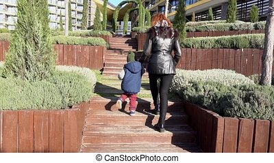 mother and young son walk through the Park on the street