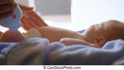 Mother applying powder to her baby boy at home 4k