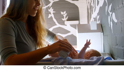Mother applying powder to her baby boy at home 4k - Side ...