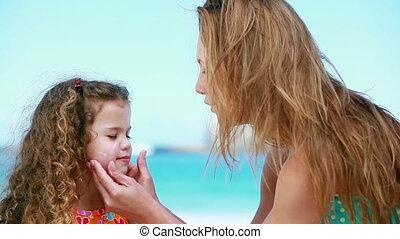 Mother applying sunscreen on a little girl