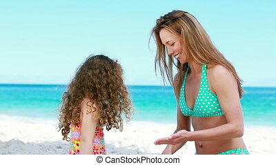 Mother applying sunscreen on her daughter on the beach