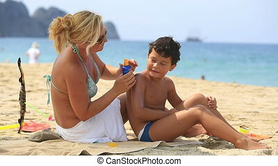 mother applying sunscreen to son