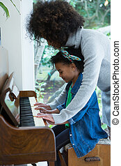 Mother assisting daughter in playing piano at home