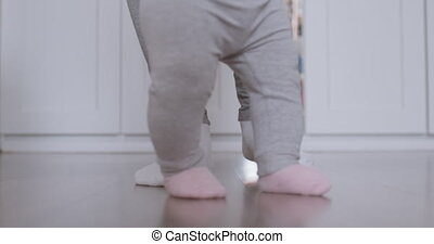Mother assisting in her baby first steps. - Mother assisting...