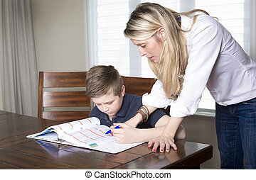 mother at a table  home helping her small son with his homework