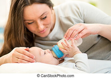 mother at home feeding baby boy with a milk bottle