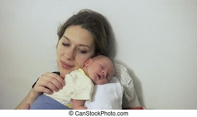 Mother At Home With Sleeping Newborn Baby Daughter