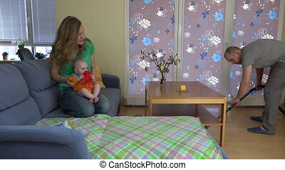 Mother woman play with baby on sofa. Father man clean floor with vacuum cleaner hoover. Everyday home works and duties. 4K UHD video clip.