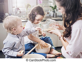 Mother baking a cake with her children